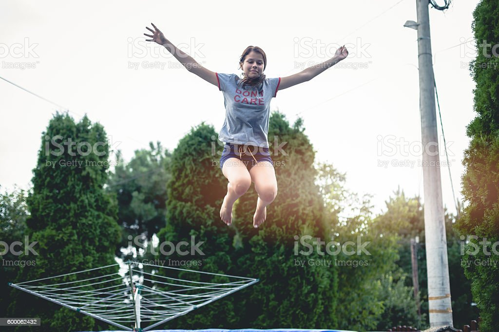Teenage girl jumping on trampoline with arms outstretched stock photo
