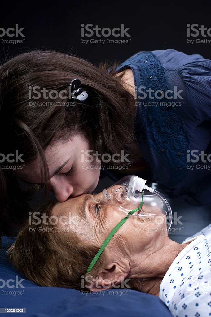 Teenage girl kissing her grandmother at the hospital royalty-free stock photo