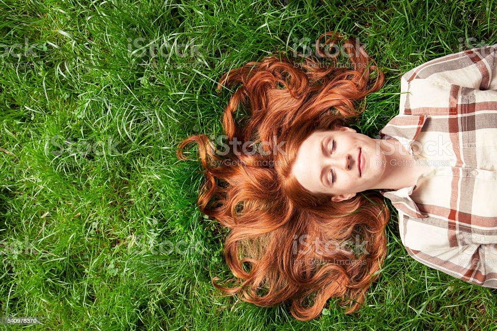 Teenage girl laying in grass stock photo