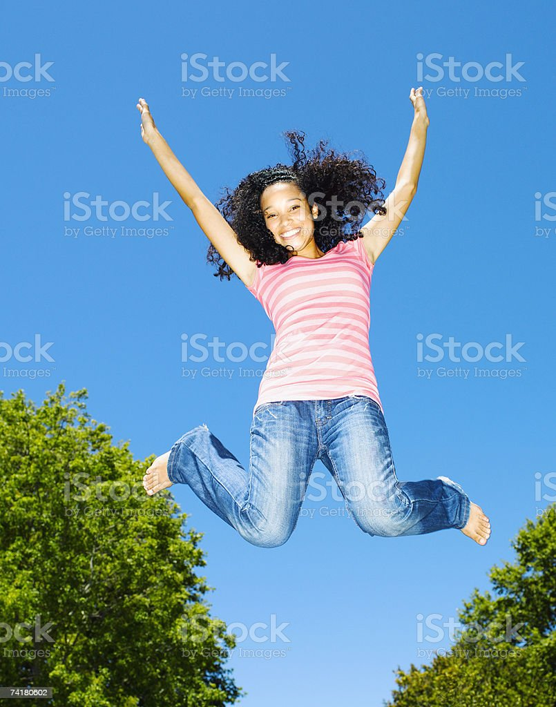 Teenage girl leaping outdoors with blue sky and trees royalty-free stock photo