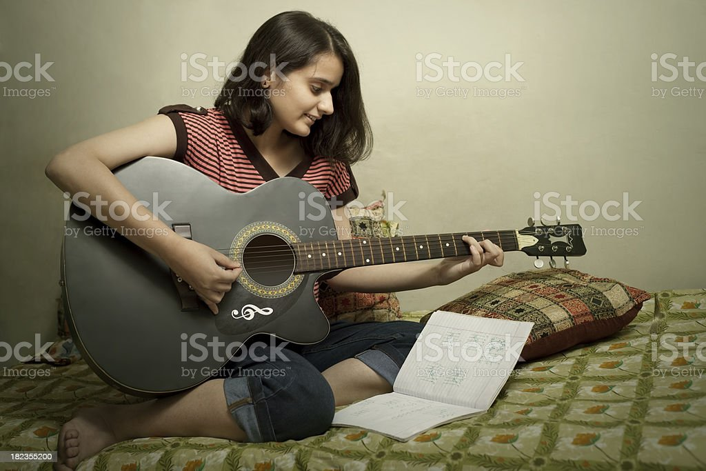 Teenage girl learning and practicing guitar at home royalty-free stock photo