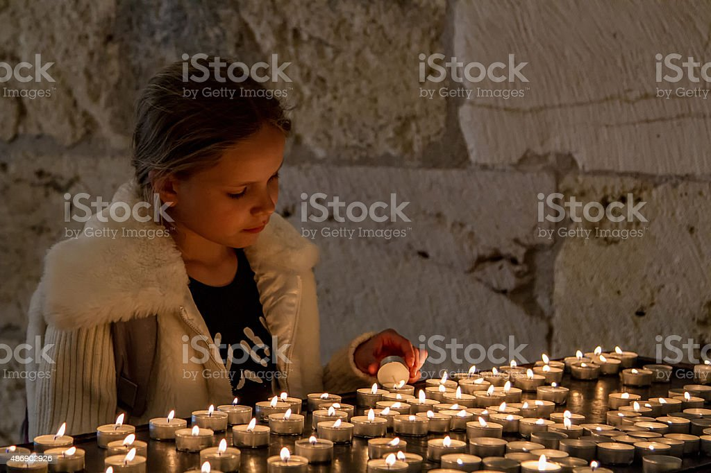 Teenage girl lights the candles stock photo