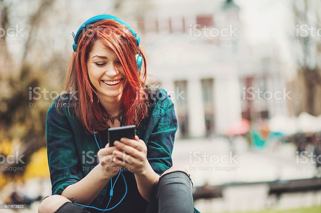 Teenage girl listening music from a smart phone stock photo