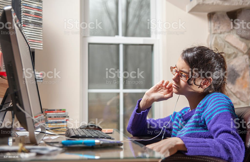 Teenage girl listening to a music on her computer stock photo