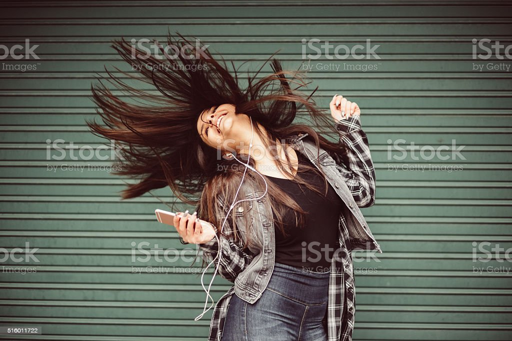 Teenage girl listening to the music and dancing stock photo