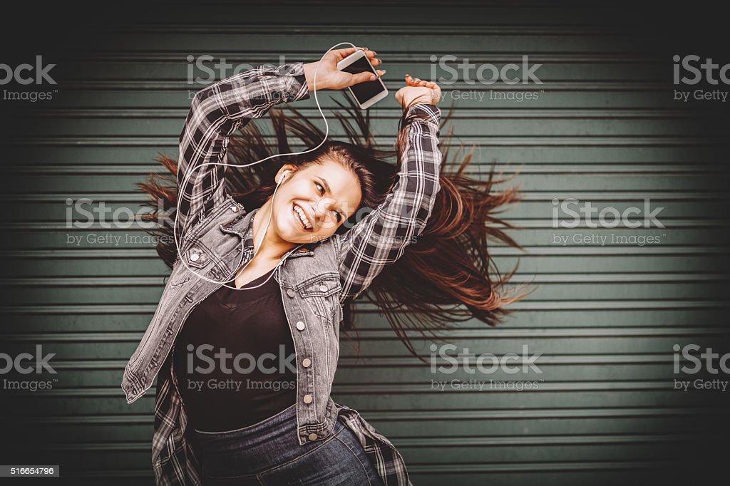 Teenage girl listening to the music and waving hair stock photo