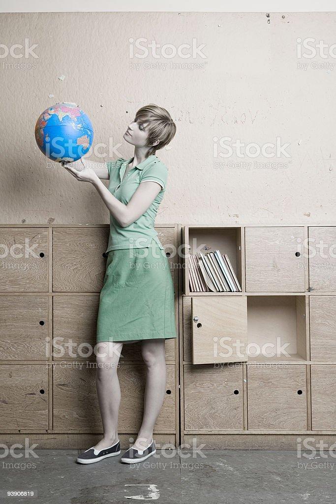 Teenage girl looking at globe stock photo