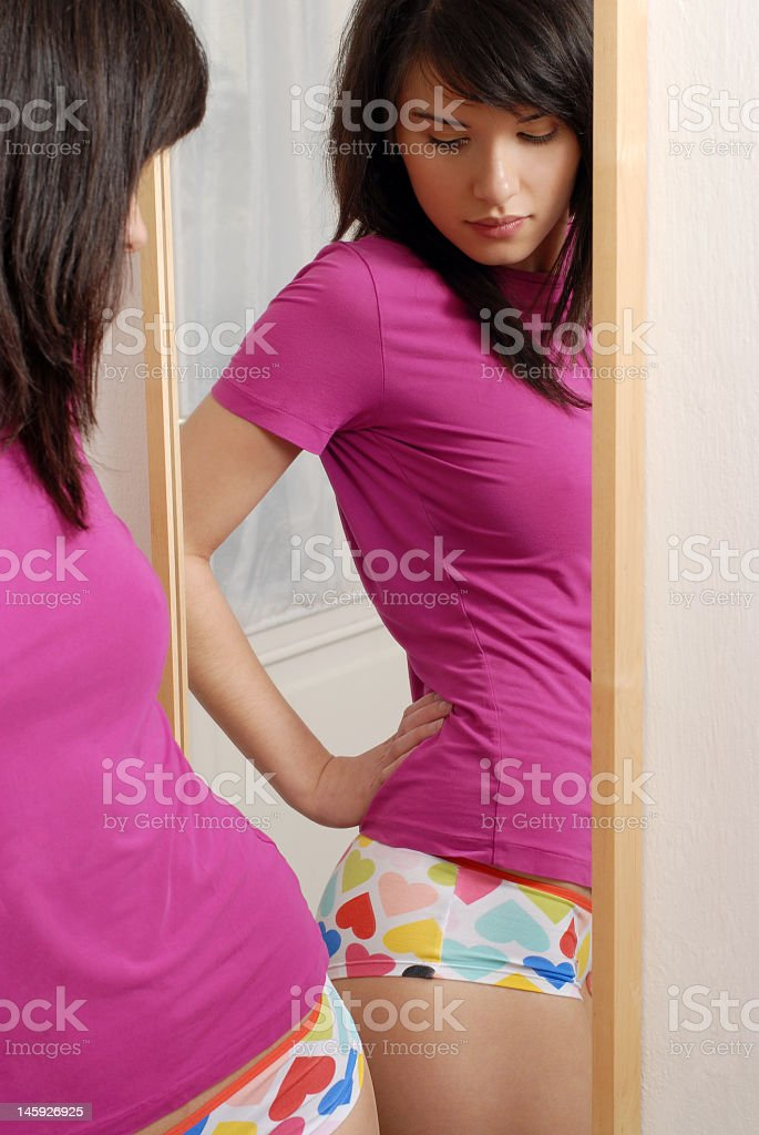 Teenage girl looking at her rear in the mirror royalty-free stock photo