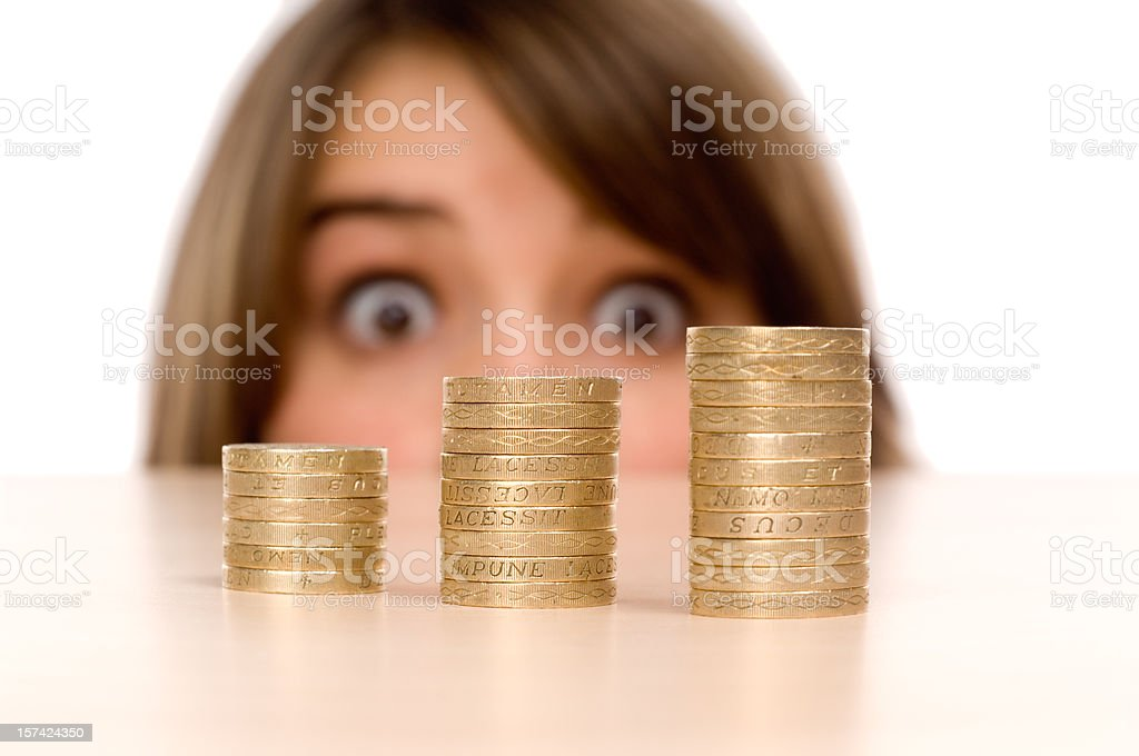 Teenage girl looking at stack of Pound coins royalty-free stock photo