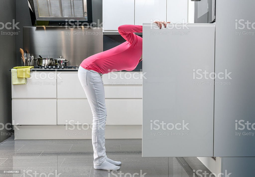 teenage girl looking into refrigerator for a snack stock photo