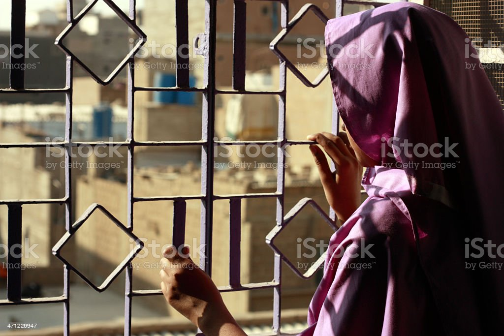 Teenage girl looking out the window at a desert city royalty-free stock photo