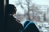 Teenage girl looking out the window