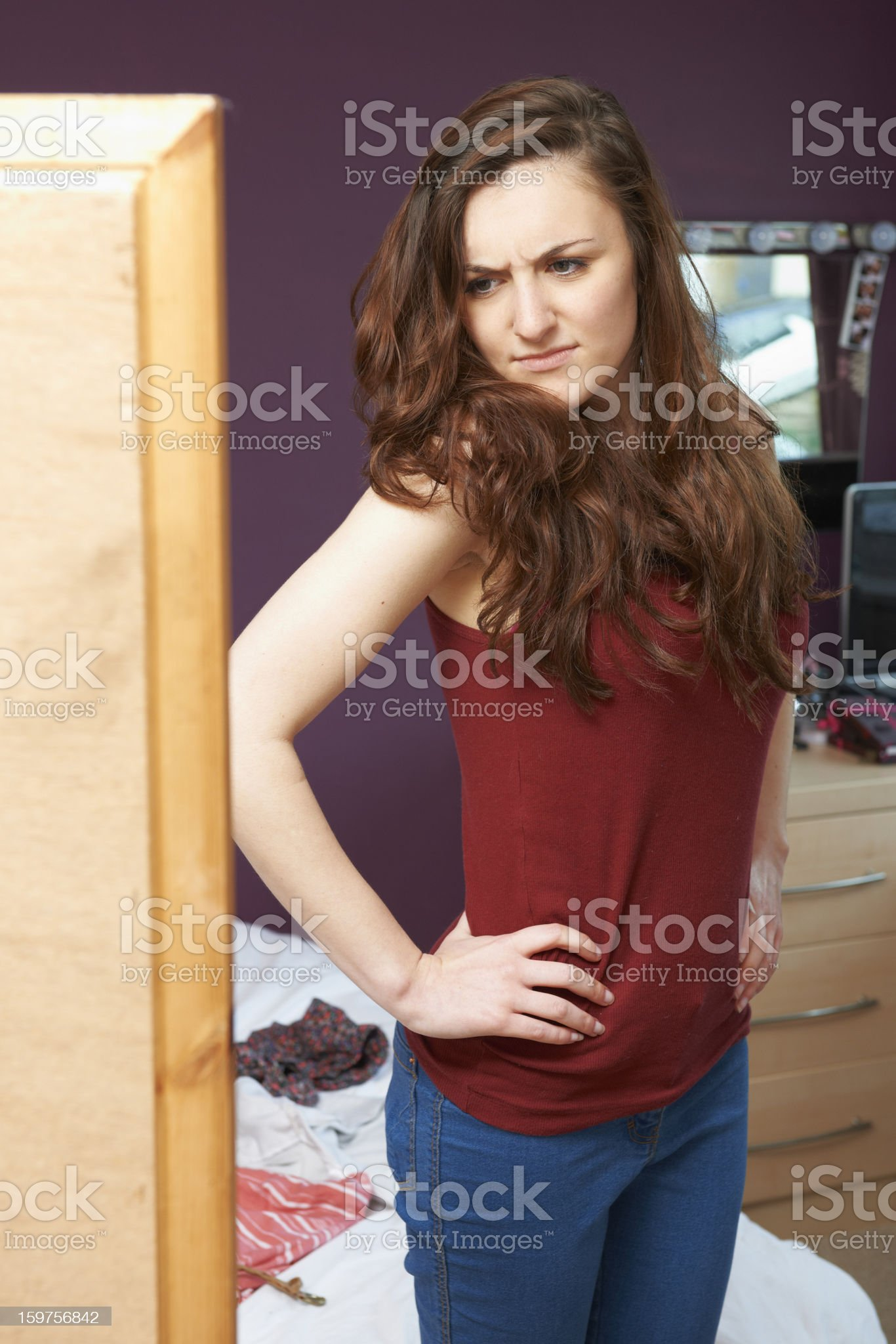 Teenage Girl Looking Unhappily At Herself In The Mirror royalty-free stock photo