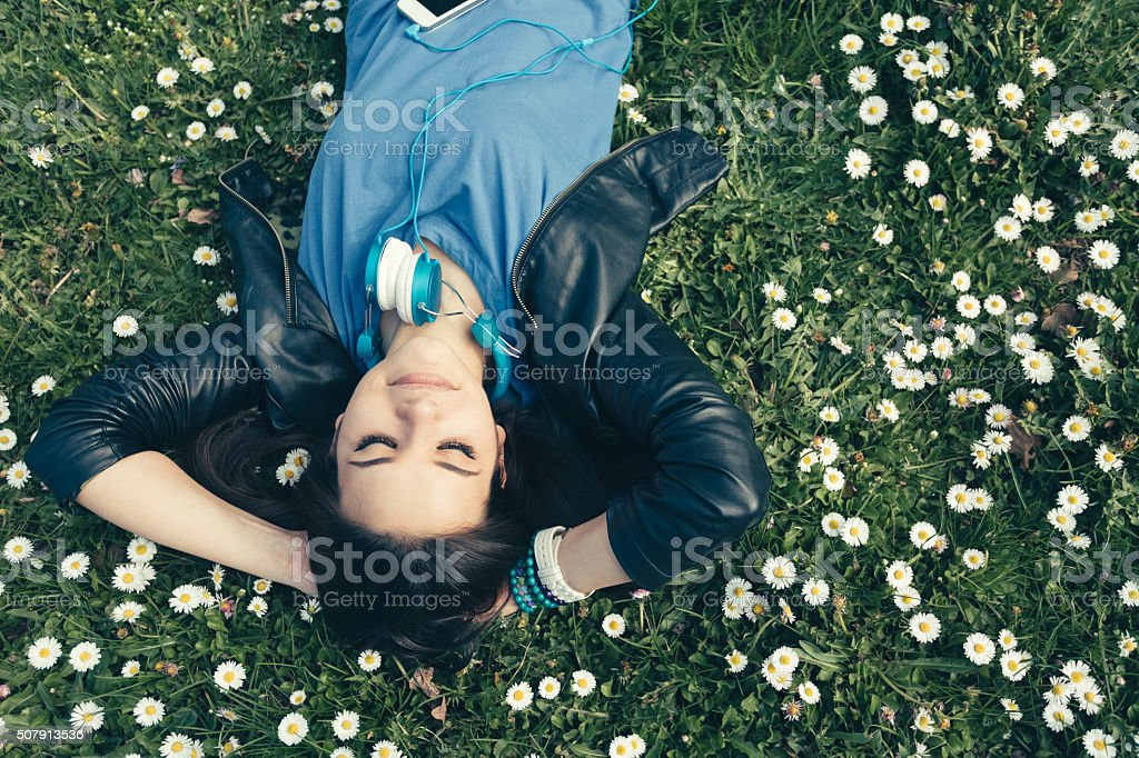 Teenage girl lying down in the grass stock photo