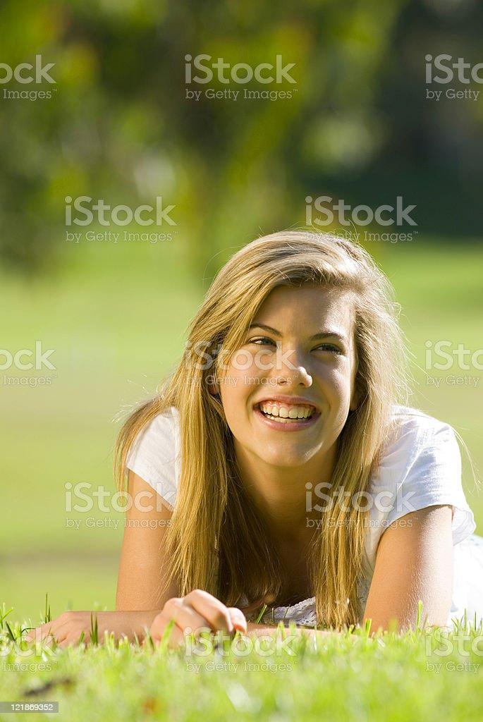 Teenage girl lying in the grass stock photo