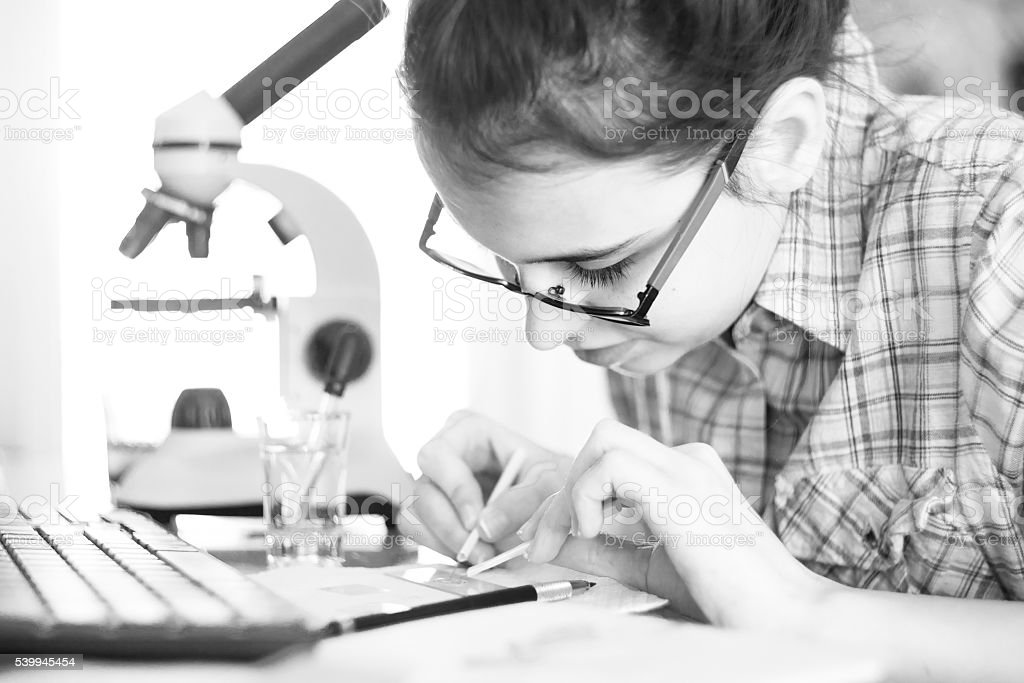 Teenage girl make homework scientific project with microscope stock photo