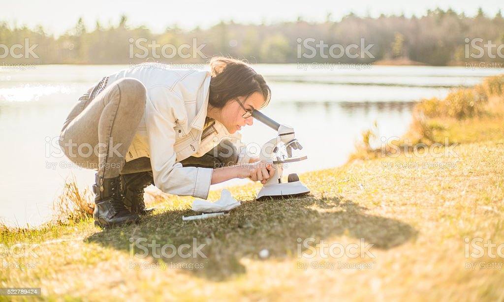Teenage girl make outdoors scientific project with microscope stock photo