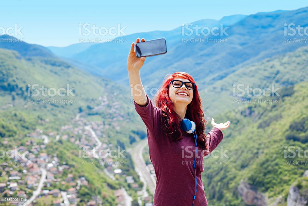 Teenage girl making a selfie in the mountain stock photo
