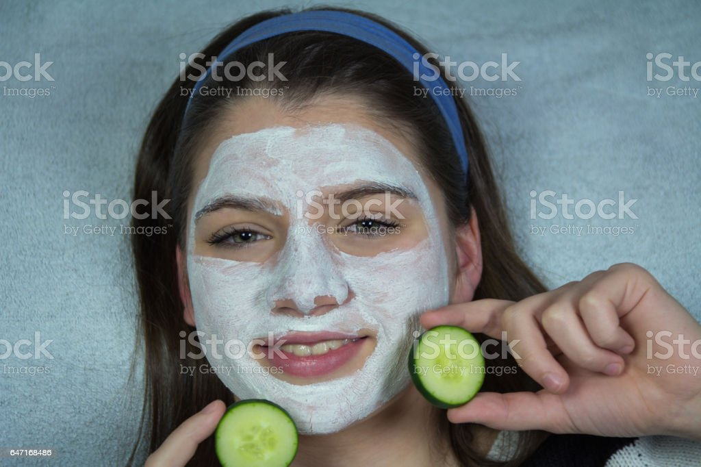 Teenage girl making facial mask stock photo