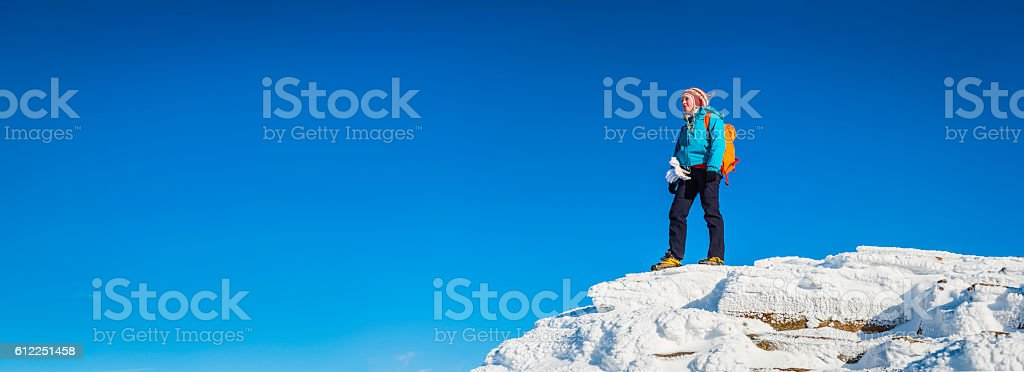 Teenage girl mountaineer on snowy mountain peak blue sky panorama stock photo
