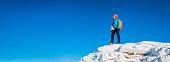 Teenage girl mountaineer on snowy mountain peak blue sky panorama