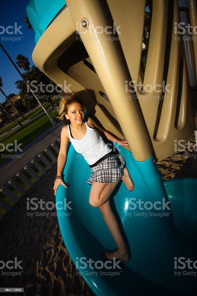 Teenage Girl on a Playground Slide royalty-free stock photo
