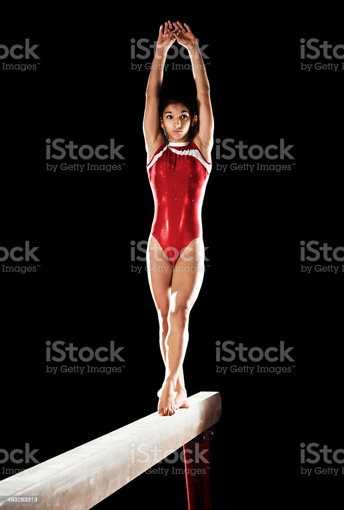Teenage girl on balance beam. stock photo