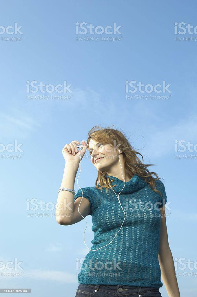 Teenage girl (16-18) outdoors, listening to MP3 player, low angle view stock photo