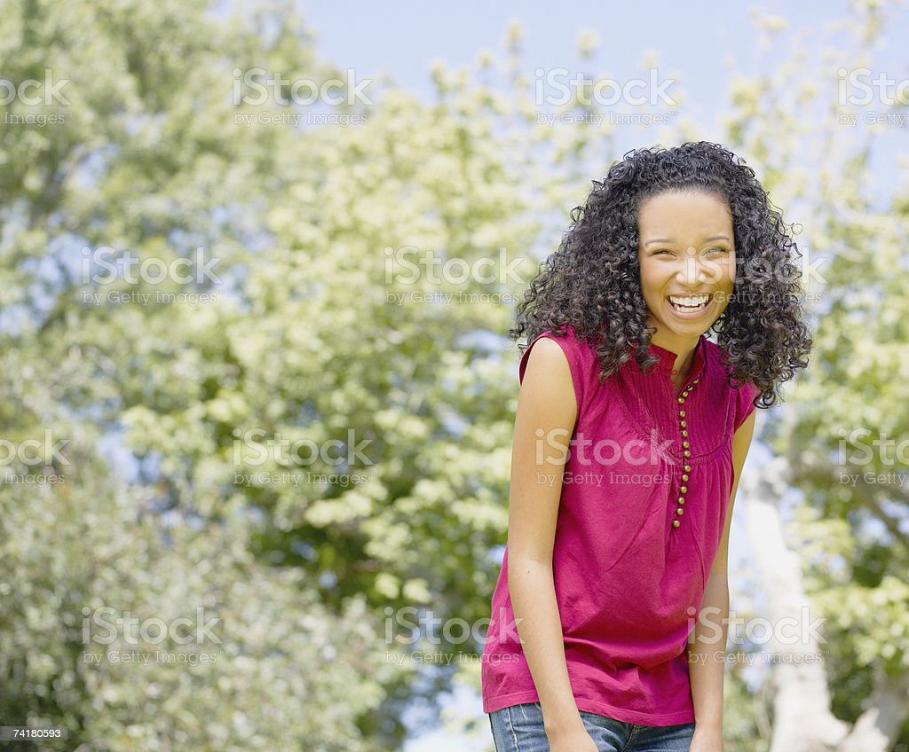 Teenage girl outdoors with trees laughing stock photo