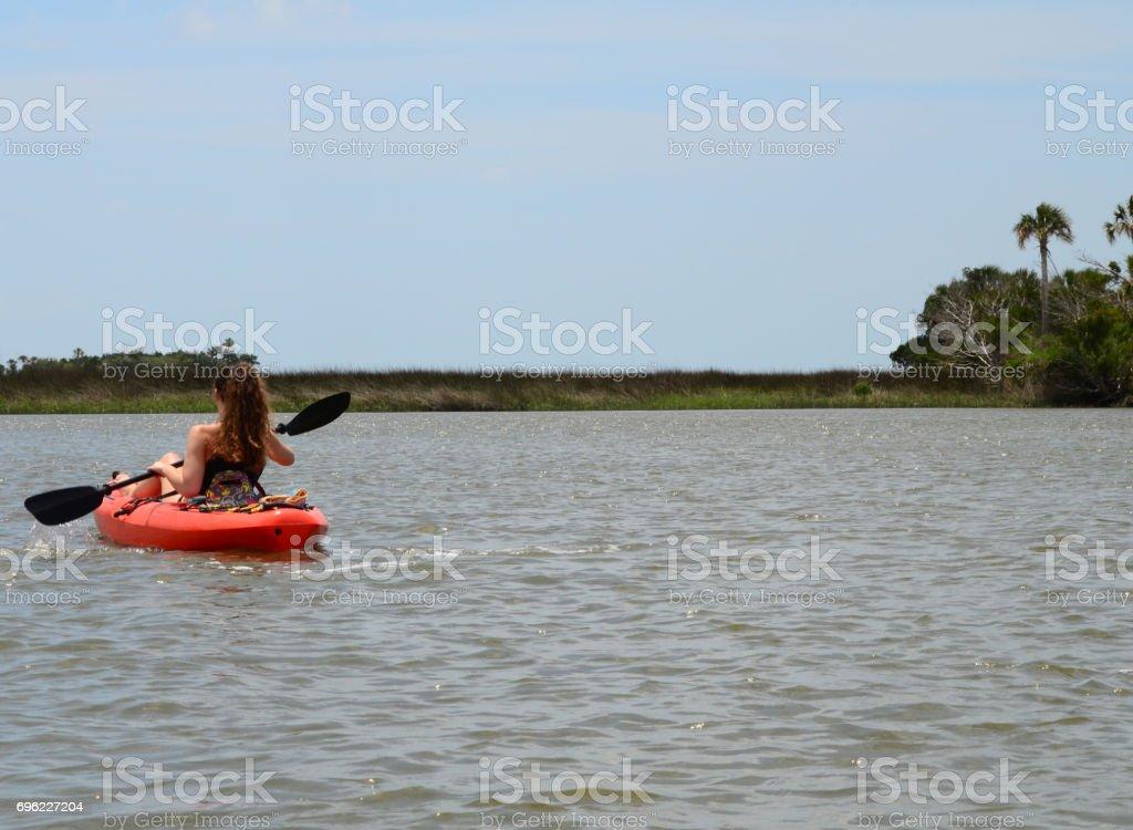 Teenage girl paddling near palm island stock photo
