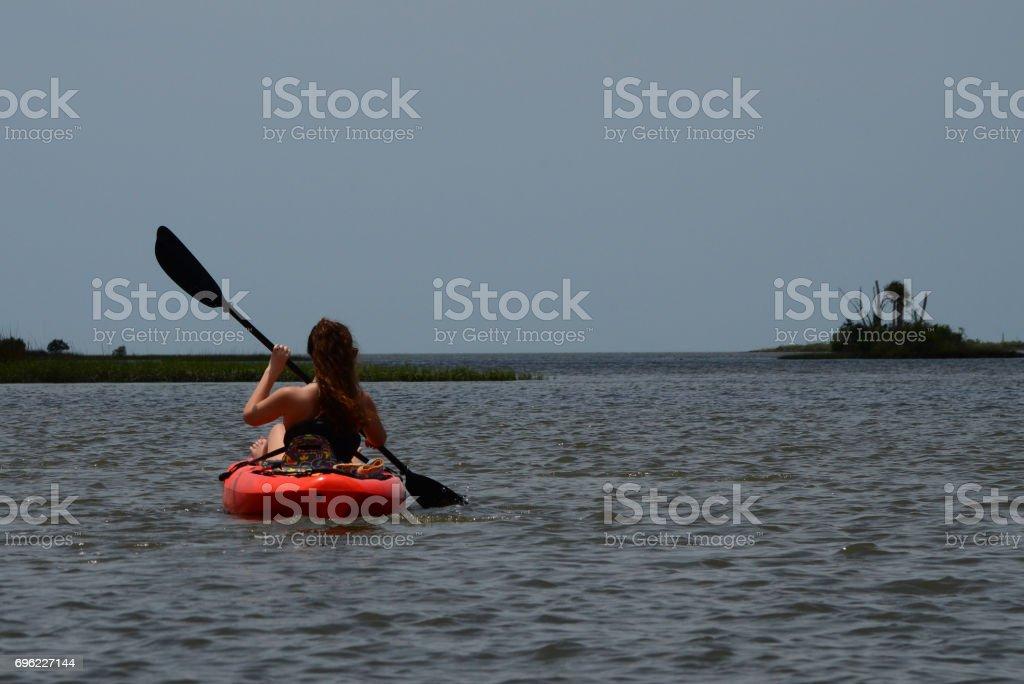 Teenage girl paddling towards palm island stock photo