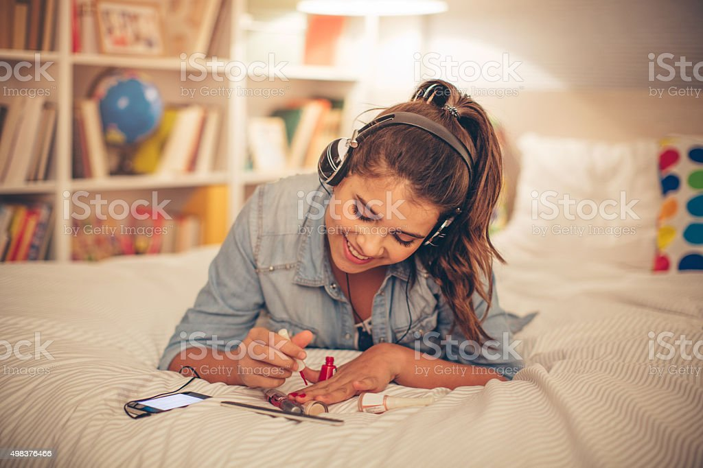 Teenage girl painting nails. stock photo
