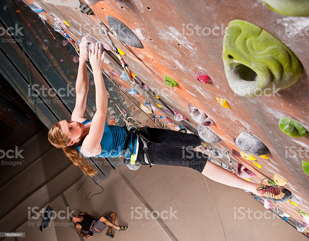 Teenage girl participating in Indoor Rock Climbing on wall stock photo