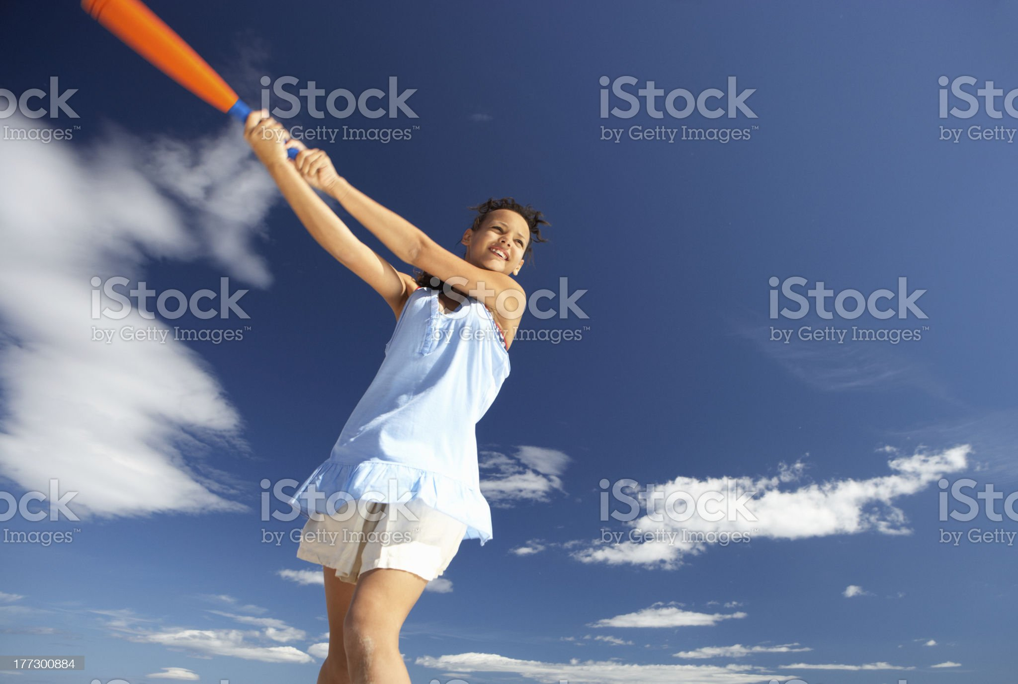 Teenage girl playing baseball on beach royalty-free stock photo