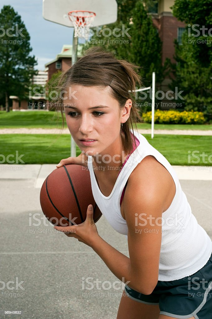 Teenage Girl Playing Basketball Outdoors royalty-free stock photo