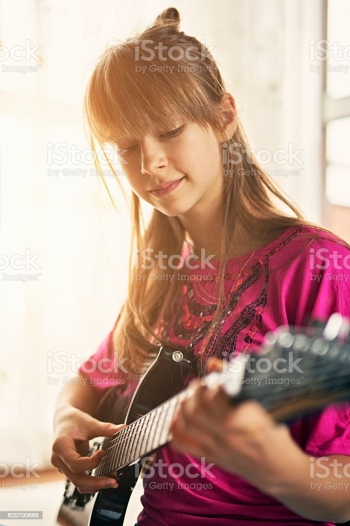 Teenage girl playing electric guitar stock photo