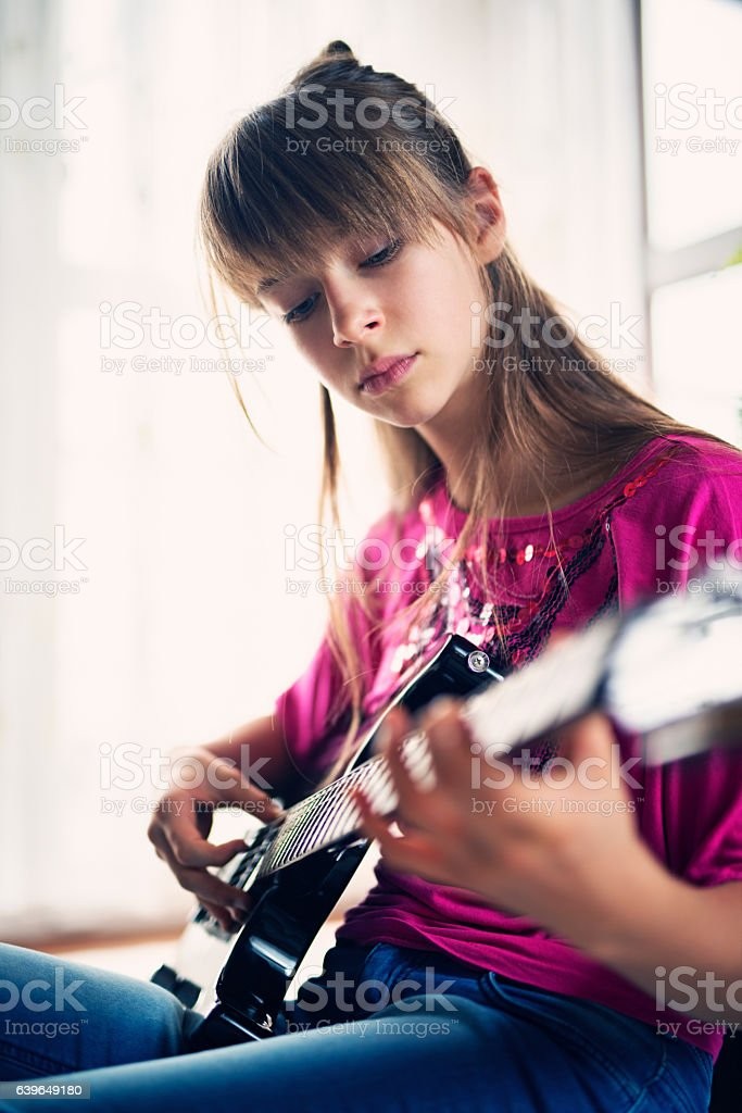 Teenage girl playing electric guitar stock photo