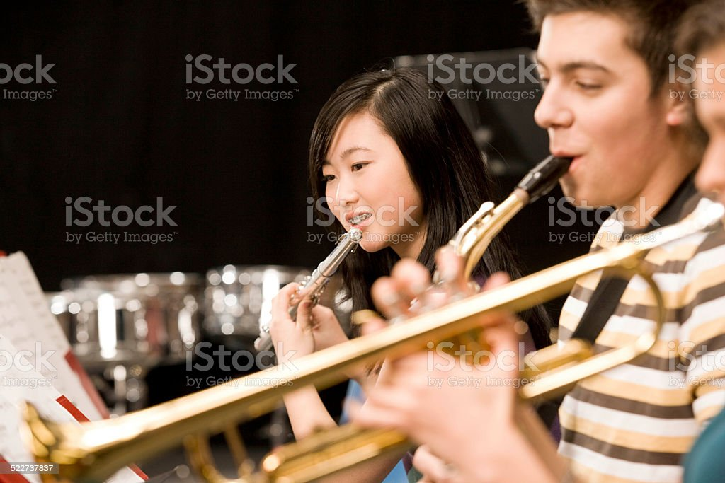 Teenage girl playing flute in high-school band stock photo