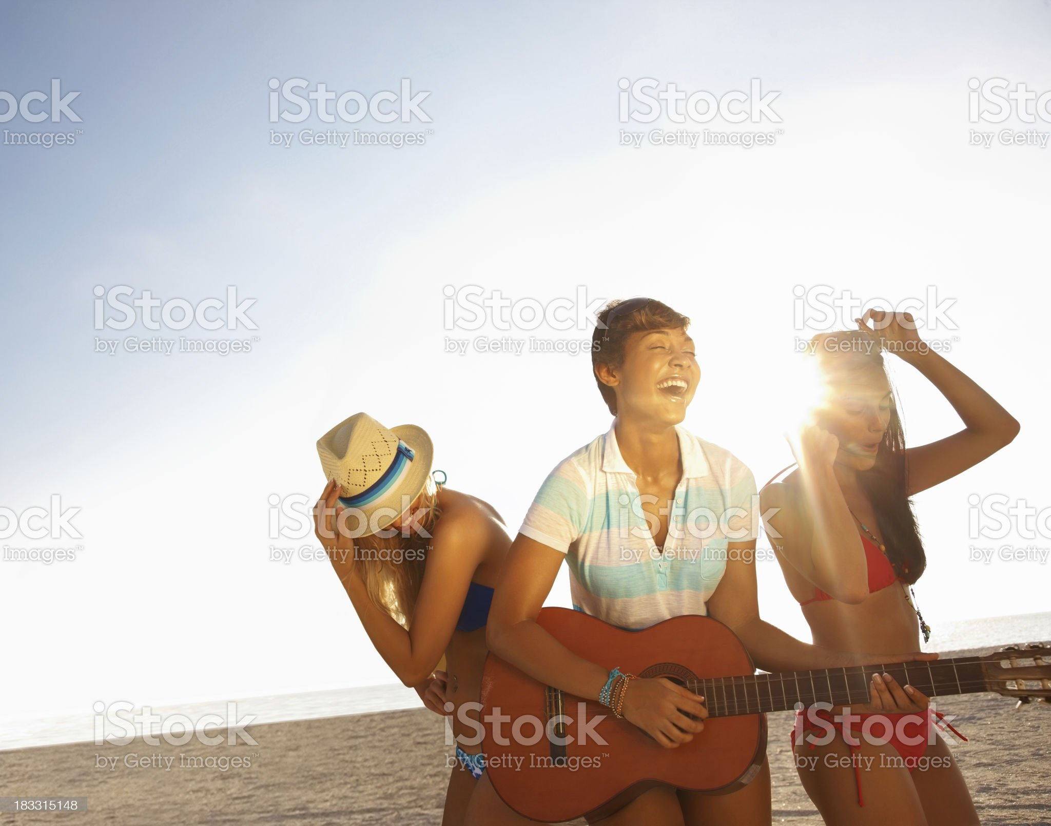 Teenage girl playing guitar while her friends dancing on beach royalty-free stock photo