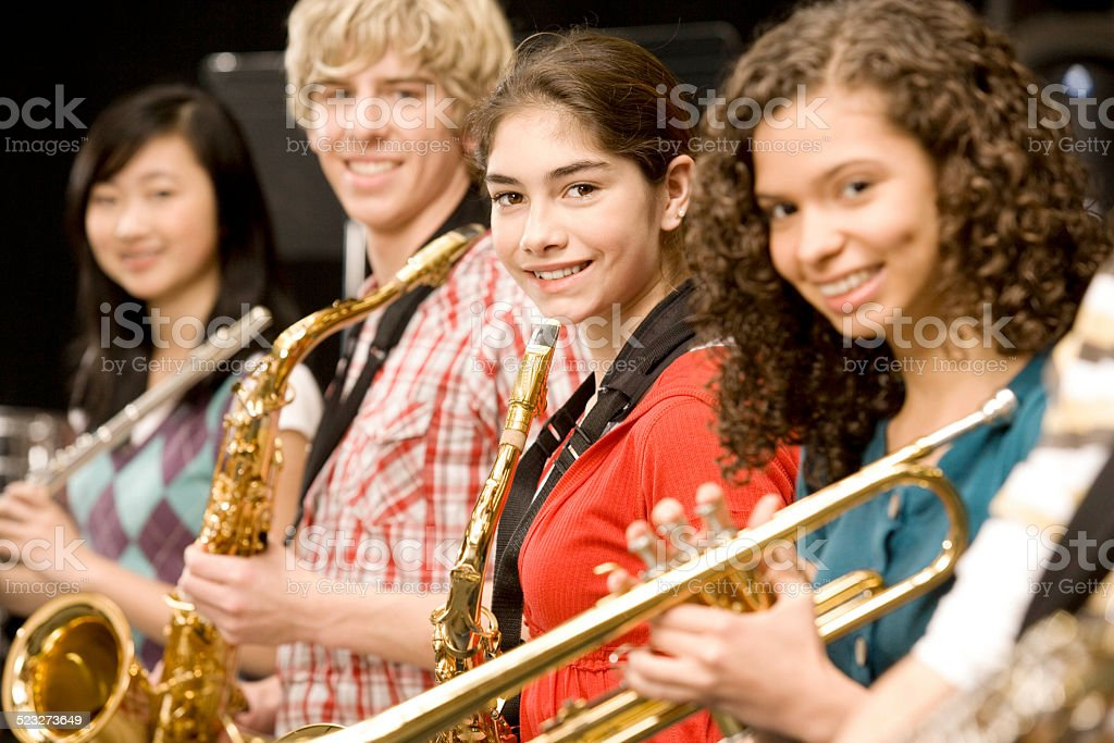 Teenage girl playing saxophone in band stock photo