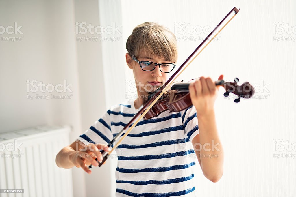 Teenage girl playing violin at home stock photo