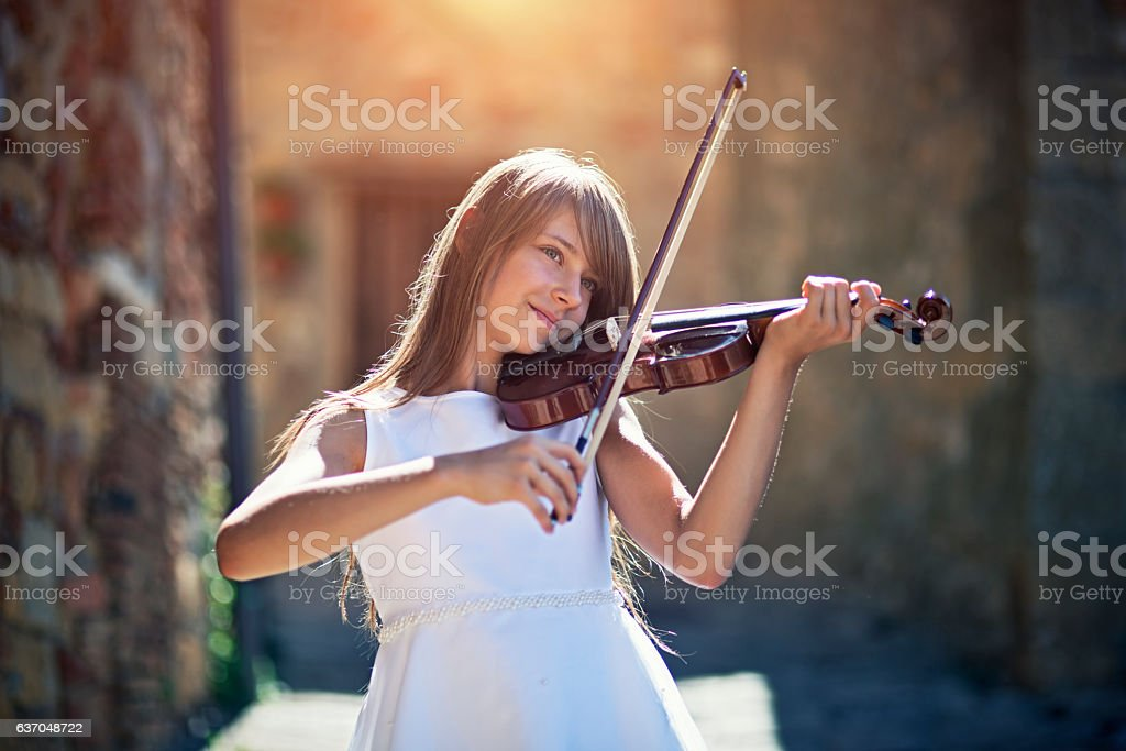 Teenage girl playing violin the sunny italian street stock photo