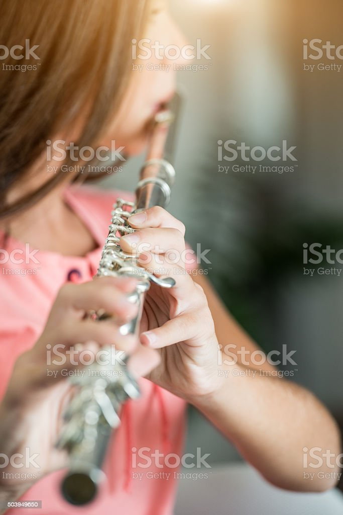 teenage girl plays the flute stock photo