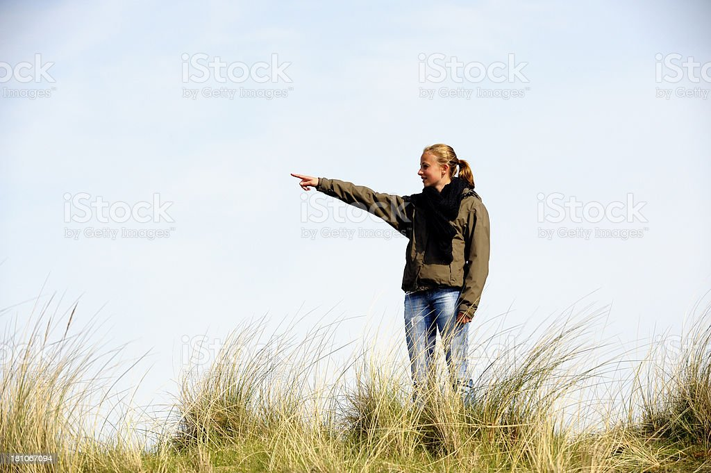 Teenage girl pointing at something in the distance royalty-free stock photo