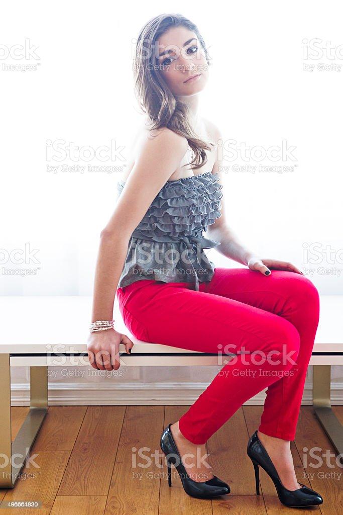 Teenage girl posing on table stock photo