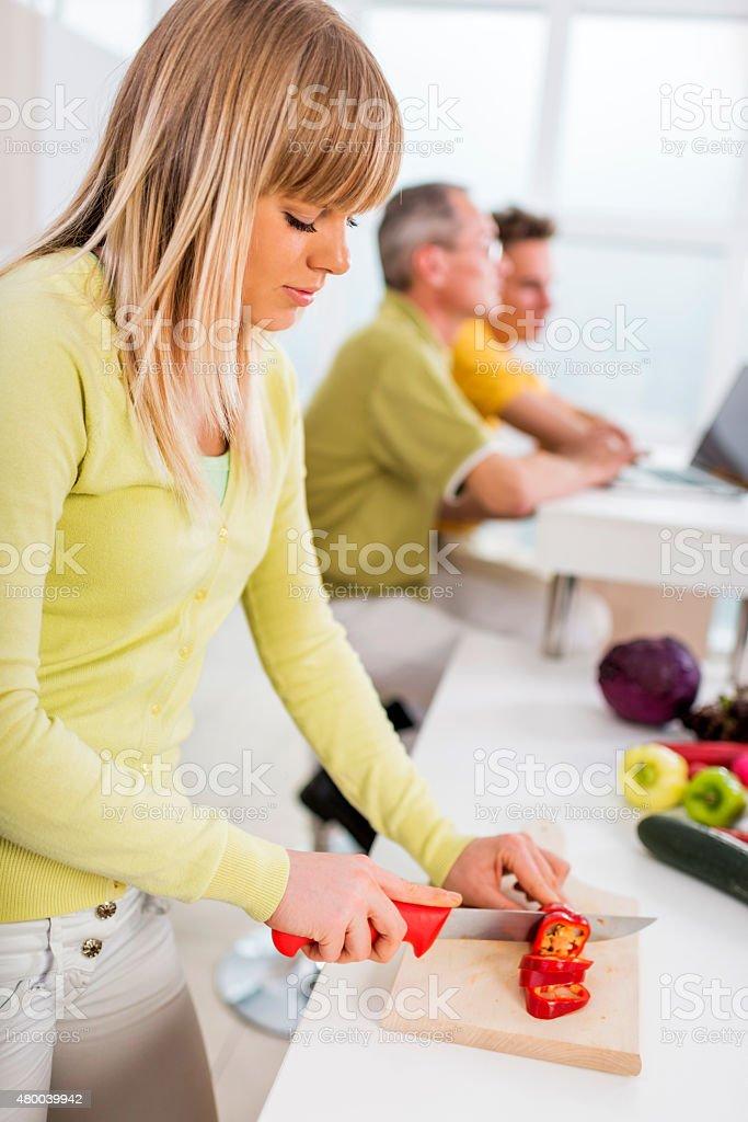 Teenage girl preparing food in the kitchen. stock photo