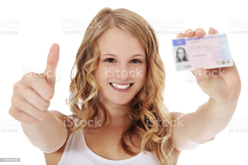 Teenage girl proudly showing her driver's license stock photo