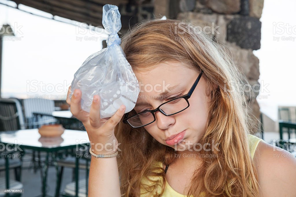 Teenage girl puts ice in plastic bag to the head stock photo