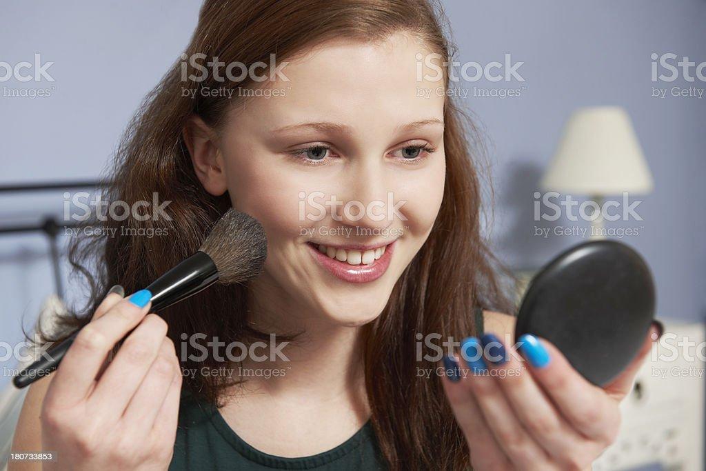 Teenage Girl Putting On Make Up In Mirror stock photo