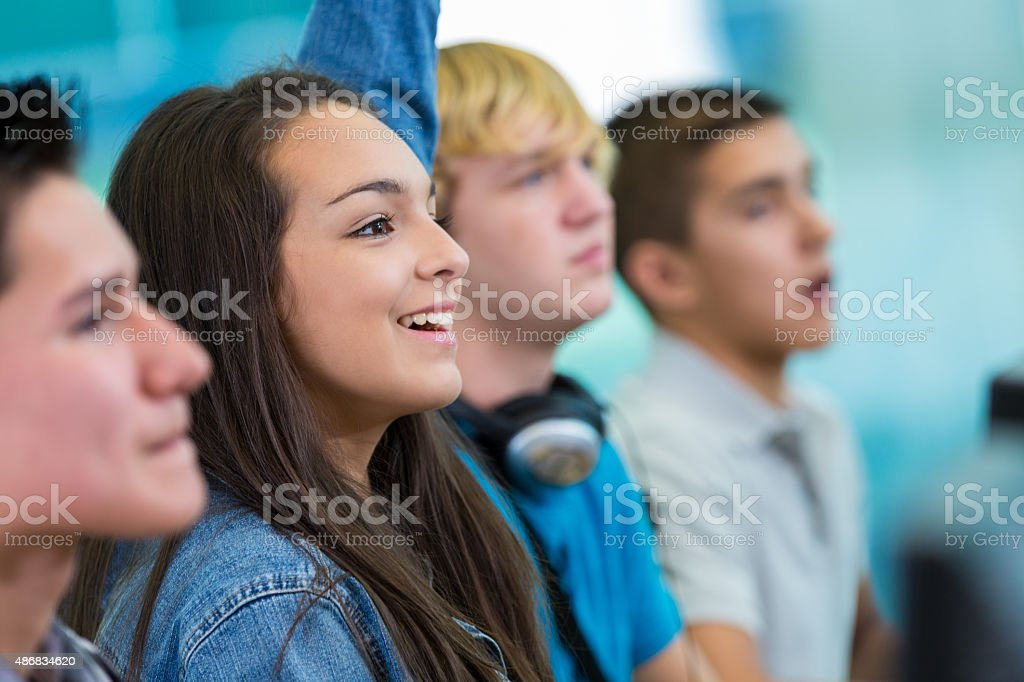 Teenage girl raising hand, asking question in high school class stock photo